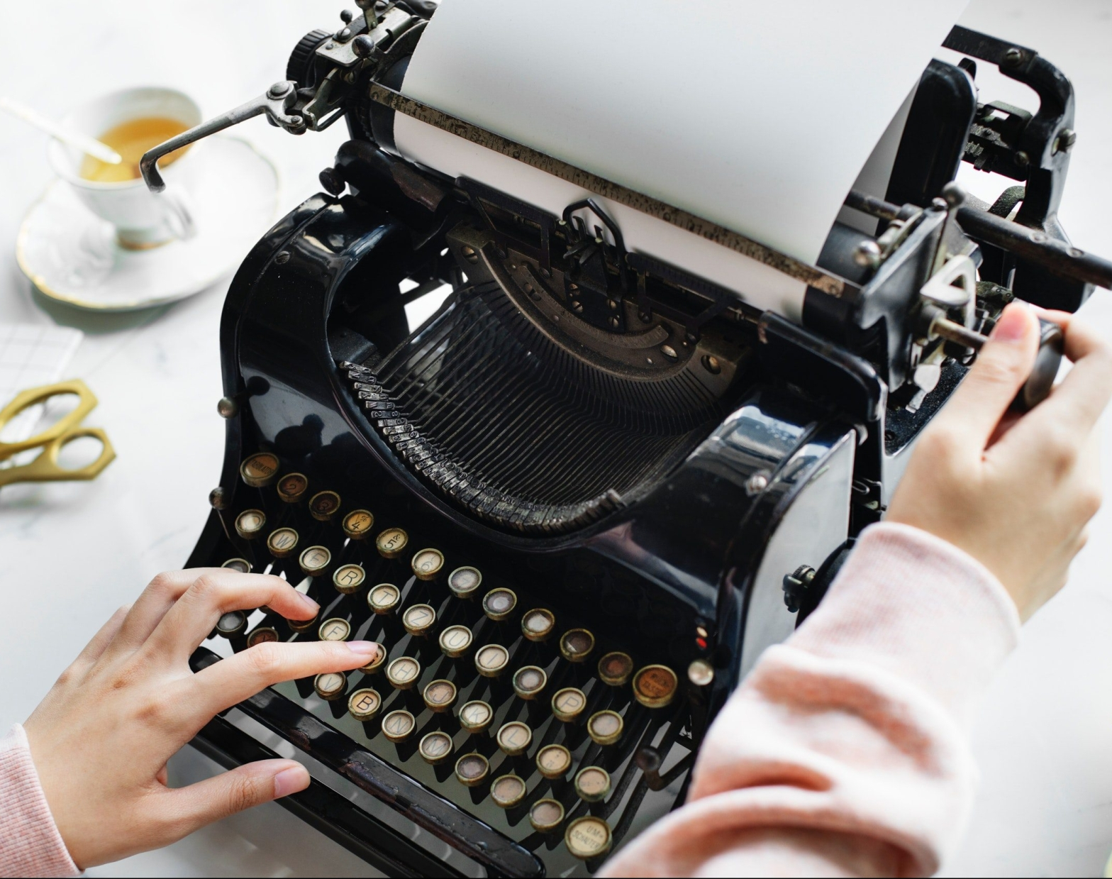 woman's hands hovering over old typewriter